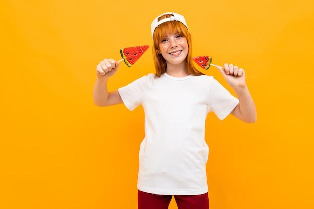 Счастливая девушка с рыжими волосами в белой футболке с белой кепкой улыбается с арбузными леденцами на желтом фоне