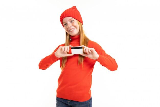 赤い髪、赤いフーディ、白い背景で隔離のカードと帽子と幸せなティーンエイジャーの女の子
