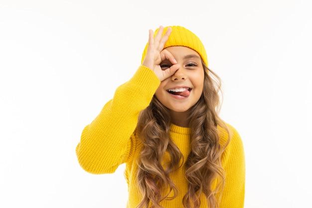 Привлекательная красивая девушка в желтой зимней шапке гримас на белом фоне