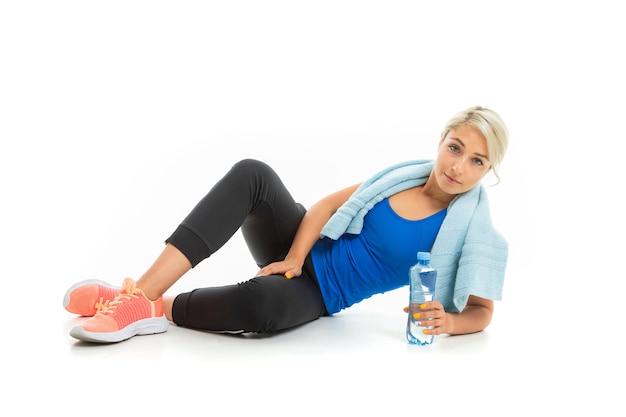 Молодая спортивная девушка со светлыми волосами расслабляется после тренировки на белом фоне