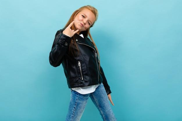 Крутая девушка-подросток в черной куртке и джинсах улыбается на синем фоне
