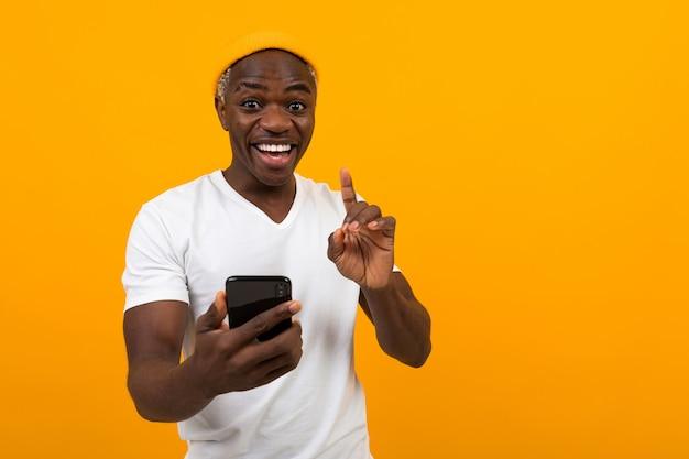 オレンジ色の背景に彼の手で携帯電話を持って笑っている黒いアメリカ人