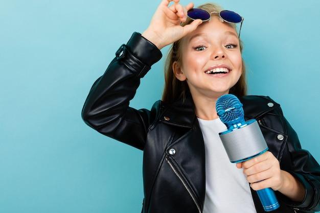 Кавказская девушка подросток с каштановыми волосами в черном пиджаке, синие очки с синим микрофоном, изолированных на синем фоне