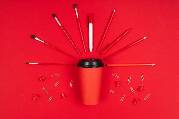 Кисти, скрепки, маркер вокруг чашки кофе, изолированных на красном фоне