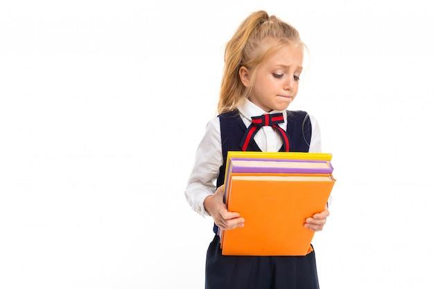 Молодая школьница со светлыми волосами держит много книг на белом фоне