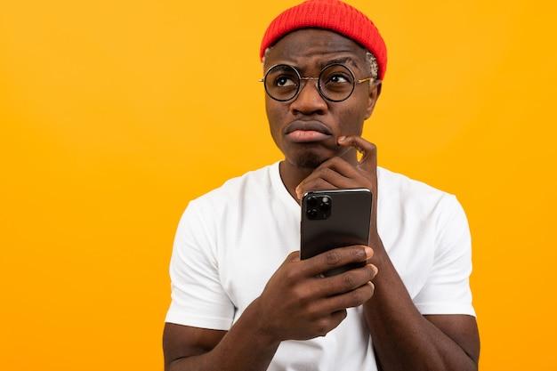Привлекательный задумчивый обаятельный черный человек в белой футболке с смартфоном в руках на желтом фоне студии