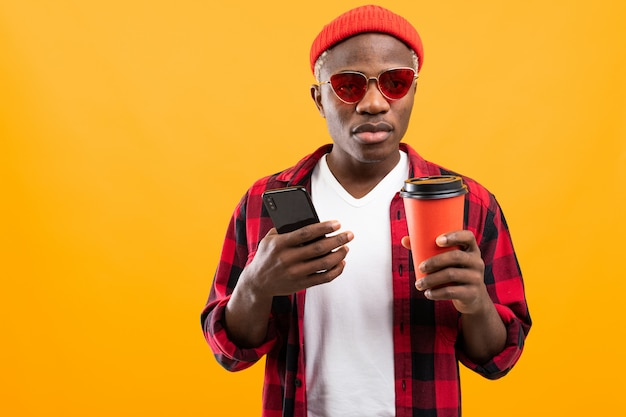電話と黄色のスタジオの背景にテイクアウトのコーヒーのグラスを持つハンサムな黒アメリカ人