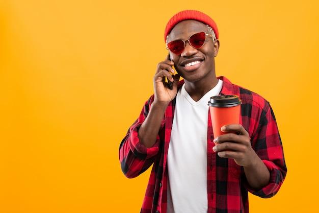 黄色のスタジオの背景に持ち帰り用のコーヒーグラスを押しながら電話で話しているハンサムな黒アメリカ人