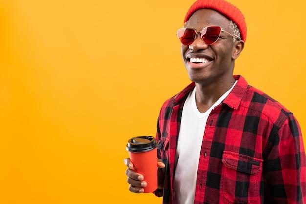 Портрет черного африканца, одетого стильно, держа бокал на желтом фоне