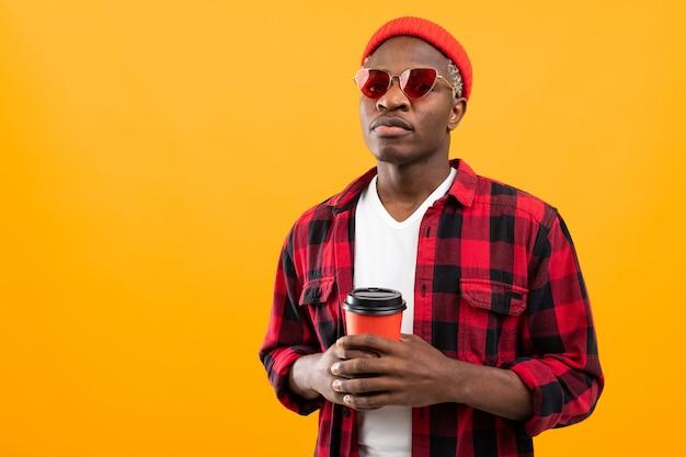 Портрет черного американца, одетого стильно, держащего стакан напитка на желтом фоне