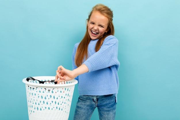 Девушка-подросток бросает свои очки в мусорное ведро и улыбается, изолированных на синем фоне