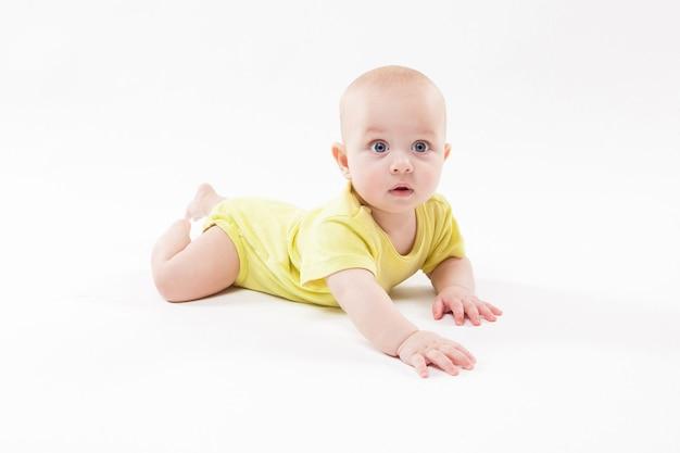 Милый ребенок лежал на земле и улыбается