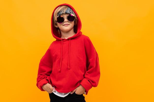 Белокурый мальчик с банданой на голове в красной толстовке и очках позирует на оранжевом фоне