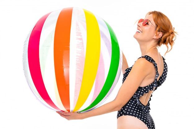 レトロな黒のワンピース水着と白地に水のための縞模様のボールとサングラスで白人少女