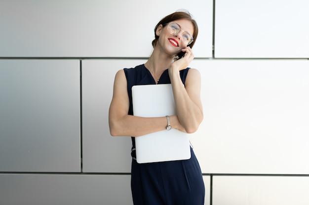 ビジネスコンセプトです。ビジネスセンターの背景の壁にラップトップで電話で話している美しいスーツに赤い唇を持つ魅力的なビジネス女性