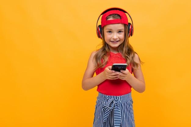 Симпатичная очаровательная молодая девушка с красными наушниками на желтом фоне