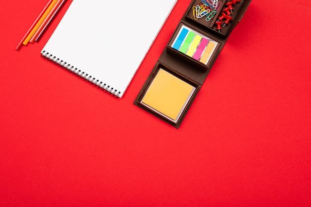 Пустая тетрадь с канцелярскими принадлежностями на красной предпосылке. офисное рабочее место
