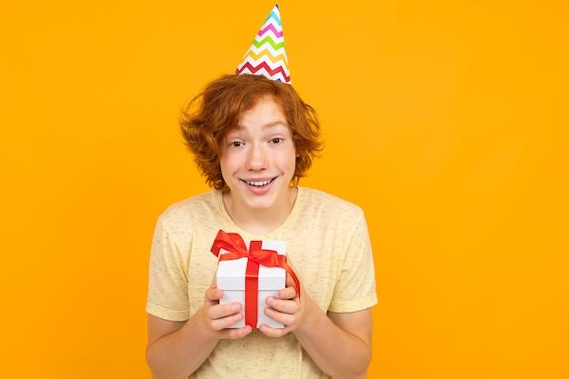 休日のコンセプトです。オレンジ色の背景に彼の手のギフトを持つ彼の頭にホリデーキャップを持つ幸せな驚き赤髪の少年