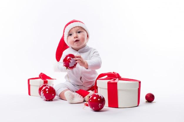 新年の帽子と白い体の美しい赤ちゃんが座っています。