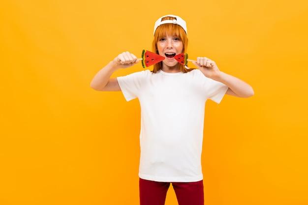 Счастливая девушка с рыжими волосами в белой футболке с белой кепкой улыбается с арбузными леденцами на палочке, изолированных на желтом
