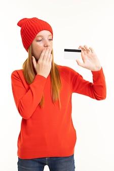 赤い髪、赤いフーディ、白で隔離されるカードと帽子と幸せなティーンエイジャーの女の子