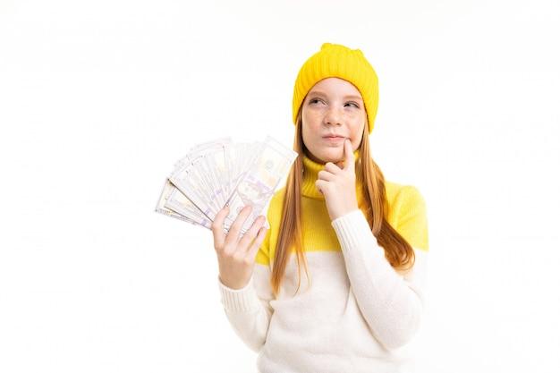 赤い髪、フーディ、帽子と幸せなティーンエイジャーの女の子はお金を保持し、白で隔離されるショッピングについて考えています