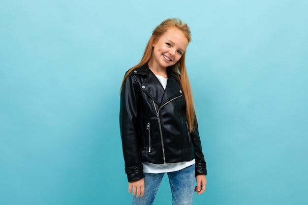 Кавказская девушка подросток в черный пиджак и джинсы улыбки, изолированных на синем
