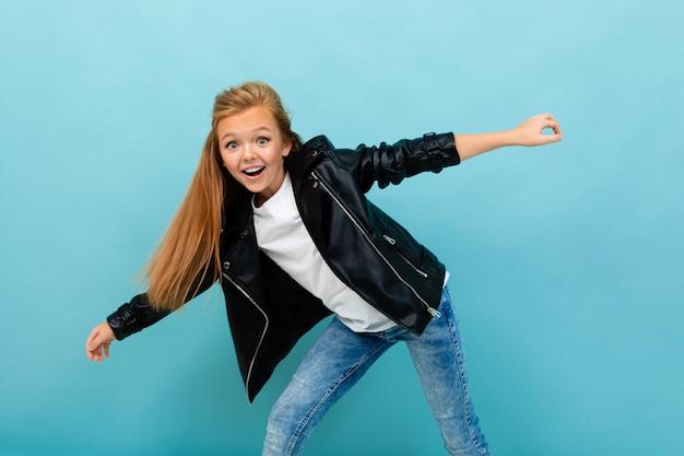 Красивая кавказская девушка подростка в черной куртке и джинсах танцует изолированный на сини