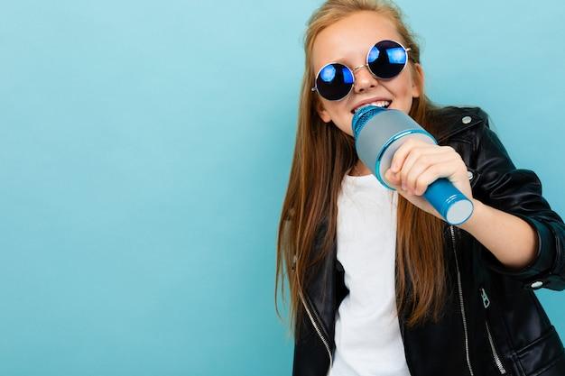 Симпатичная девушка в черной куртке, синие очки поет песни с синим микрофоном, изолированных на синем