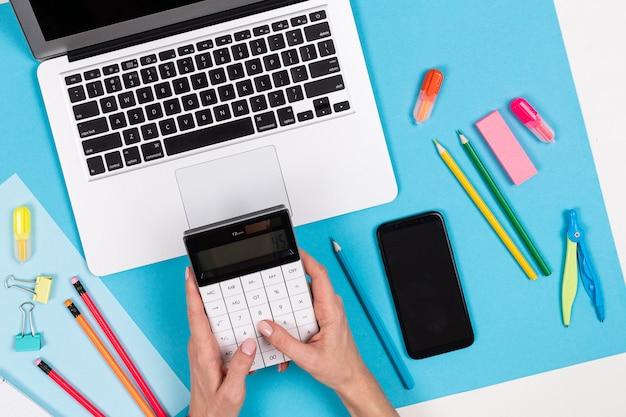 電卓、ラップトップ、携帯電話、青と白で隔離される文房具