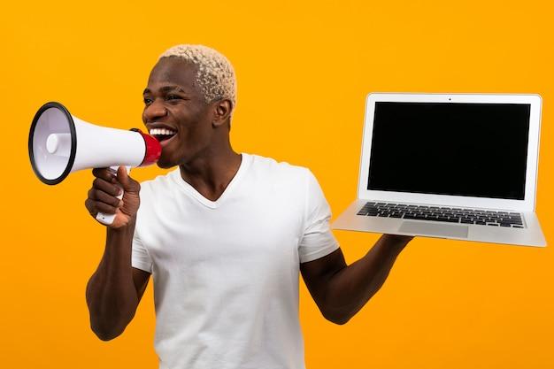 Африканский черный человек с белыми волосами говорит в мегафон, держа ноутбук для рекламы на желтой студии