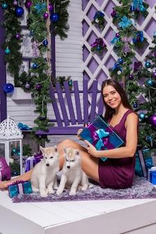 紫色の敷物の上に座ってブルゴーニュドレスの脚の長いブルネット