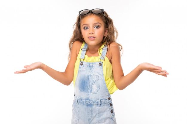 カジュアルな表情の女の子が白の驚きで肩をすくめる