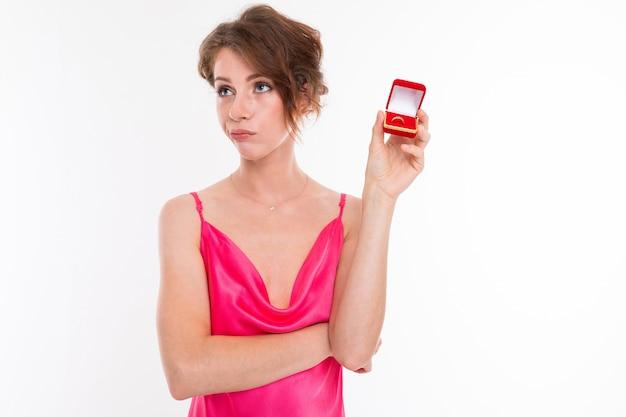 Милая девушка в розовом платье показывает коробочку с кольцом на белом