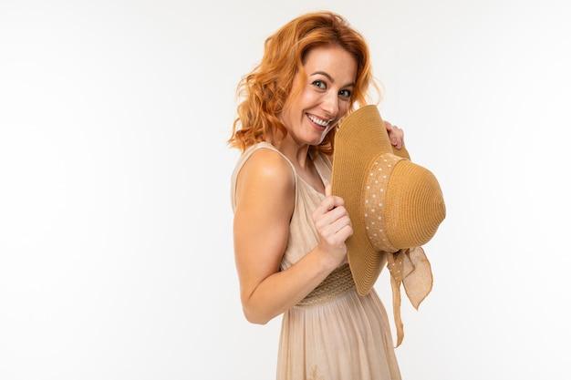 白の彼女の手で夏の帽子とドレスを着たかわいい幸せな魅力的な美しいブロンドの女の子の肖像画
