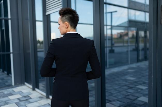 ジャケットを着た短髪のビジネスウーマンが後ろを向いて立って、近代的なオフィスビルの正面玄関まで歩いています
