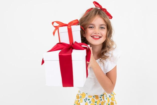 バレンタインデーのコンセプトです。彼女がちょうど白で受け取った贈り物を保持している美しい魅力的な女の子の肖像画