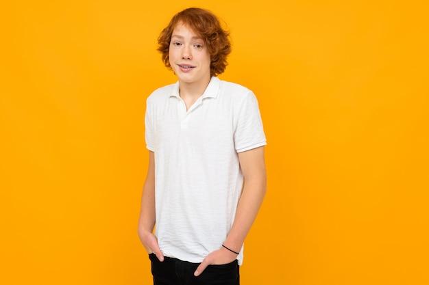 Рыжий красивый кавказский подросток мальчик в белой футболке на желтом с копией пространства