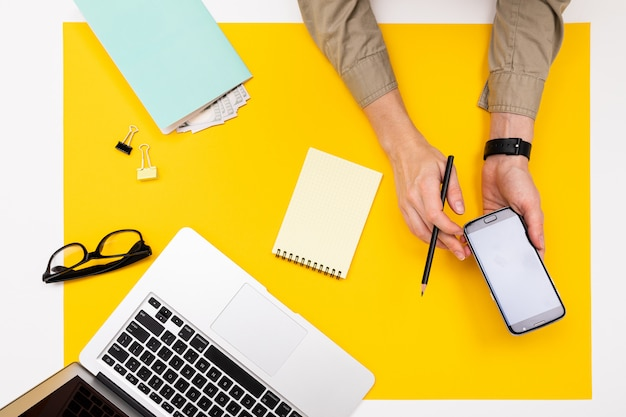 仕事場。黄色の表面に携帯電話で手、お金、ノートパソコン、メガネ、ノートブックのトップビュー