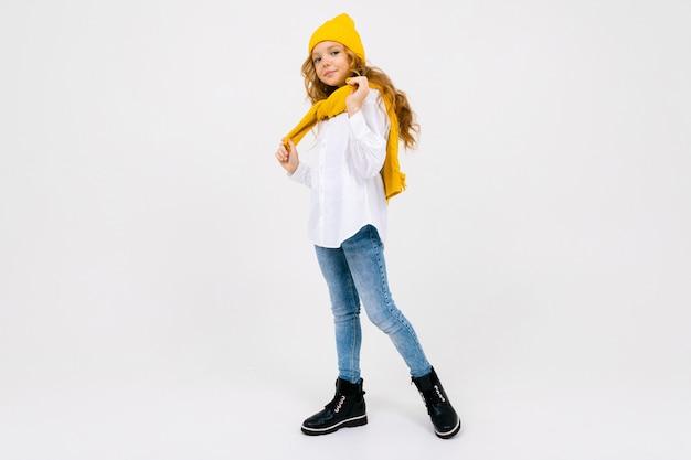 Стильная привлекательная кавказская девушка в белой рубашке и синих джинсах и желтой шляпе в сапогах позирует на белой студии в полный рост с копией пространства