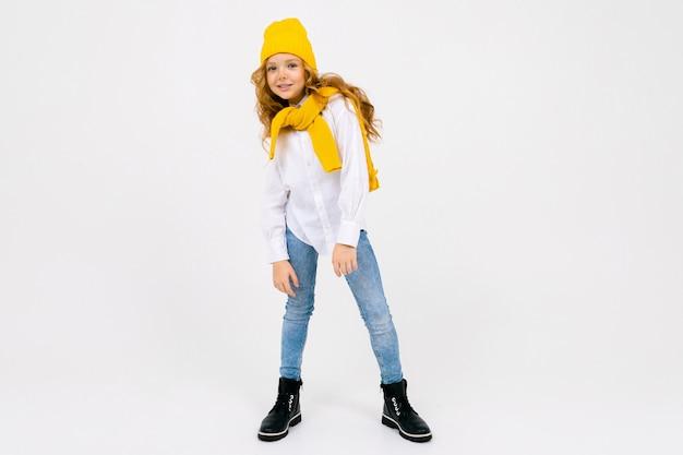 Стильная привлекательная мечтательная кавказская девушка-подросток в белой рубашке и синих джинсах и желтой шляпе в сапогах на белой студии во всю длину с копией пространства