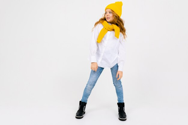 Стильная привлекательная мечтательная кавказская девушка-подросток в белой рубашке и синих джинсах и желтой шляпе в сапогах смотрит вдаль на белую студию с копией пространства