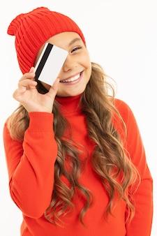 赤い帽子とフーディで幸せな白人少女は白のクレジットカードを保持しています。