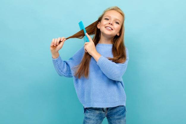 青い壁に髪をとかす魅力的なヨーロッパの女の子