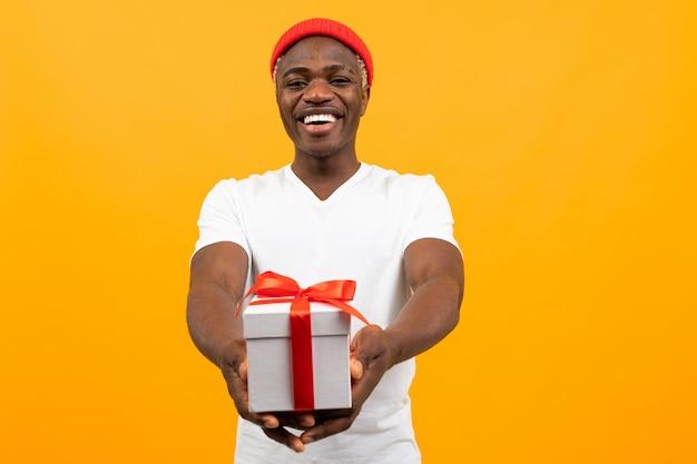 Милый темнокожий мужчина с улыбкой в белой футболке протягивает подарочную коробку с красной лентой на желтом с