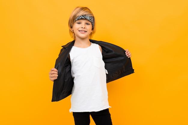 Стильный юный юноша в черном пиджаке и белой футболке кладет руки себе на грудь