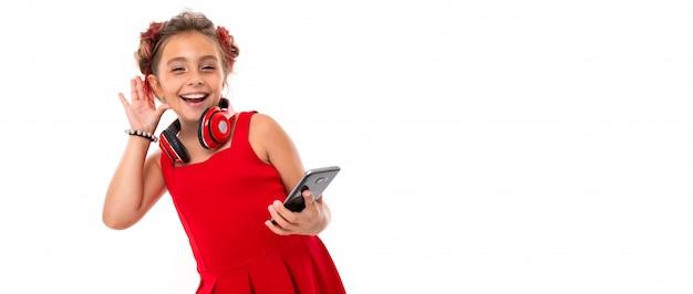 Маленькая кавказская девушка слушает музыку с большими красными наушниками на белом