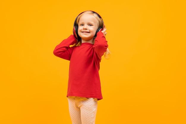 Красивая девушка с длинными волосами улыбается и слушает музыку, картинка, изолированная на желтом
