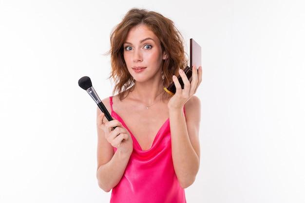 Молодая красивая девушка делает макияж, изолированные на белом