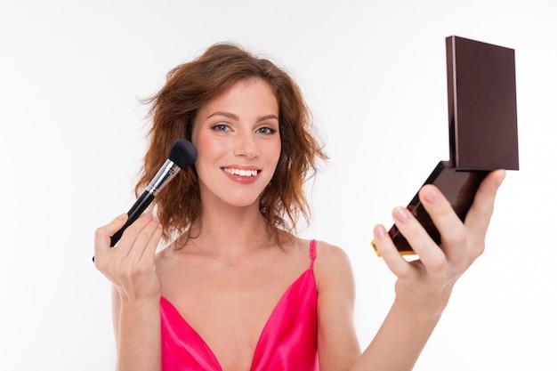 Молодая красивая девушка делает макияж с маленьким зеркалом на белом
